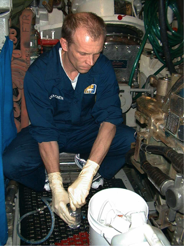 Figure 2: Oceanographer, Steve Okkonen, fills water bottles with sea water using a through-hull valve in the submarine's torpedo room. Image courtesy of U.S. Navy Arctic Submarine Laboratory.