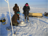 Scientists installing an ice mass balance buoy (IMB)