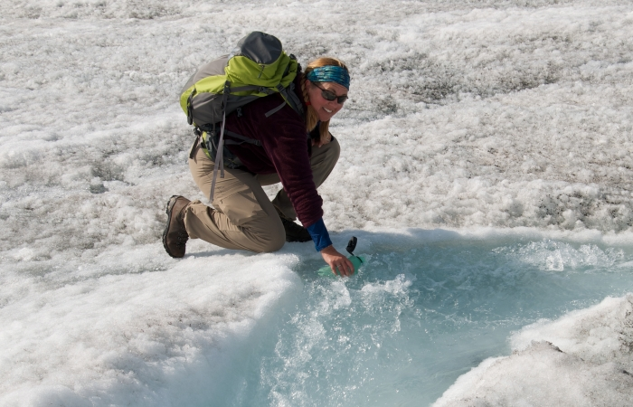 Teacher Tina Ciarametaro fills up her water bottle with freshly melted glacial water. Sukkertoppen Ice Cap, Greenland. Photo by Tina Ciarametaro (PolarTREC 2014), courtesy of ARCUS.