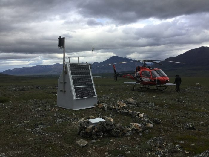 Photo of TA station E22K, located near Anaktuvuk Pass in the Brooks Range, on 18 July 2018. On this service trip, IRIS staff installed two additional lithium batteries and a wind turbine for extra power (the black cylinder on the left). The box in the foreground marks the top of the seismometer borehole. Photo by Max Enders, IRIS