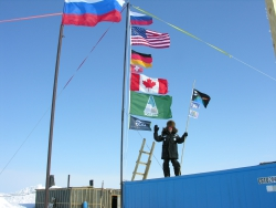 Tim Martin poses with expedition flags and school flags at Camp El'gygytgyn, Chukotka, Russia.
