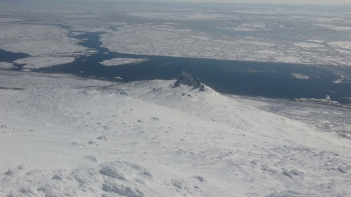 4 May 2014 - Looking down at the narrow strip of land fast ice present at the Cape. Open water exists along the shorefast ice edge and leads separate large floes.