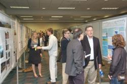 Conference participants discuss research during a poster session.