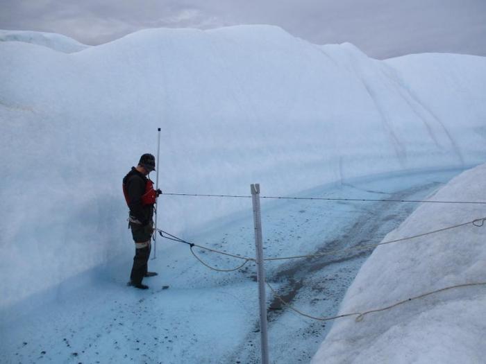Image 2. Sasha Leidman taking superficial stream measurements on the Greenland Ice Sheet. Photo courtesy of Sasha Leidman.