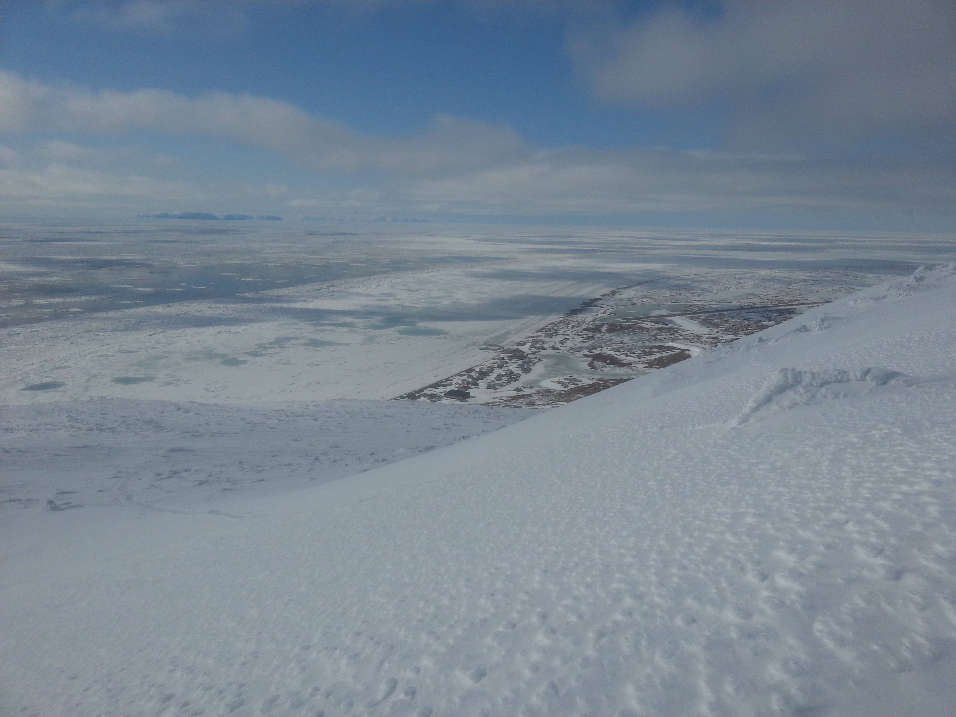 4 May 2014 - Looking WNW across the Bering Strait. Shorefast ice shows evidence of thaw from the preceding week, with large melt ponds showing up as light blue in color.
