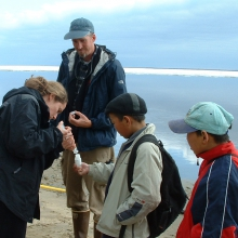 PolarTREC researcher Max Holmes collects water samples with the help of local Zhigansk students.