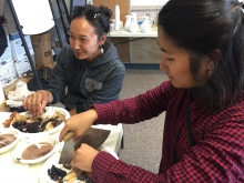 Project team members Charlene Apok and Sarah Huang enjoying a meal of traditional foods in Utqiaġvik, Alaska. Photo courtesy of Courtney Carothers.
