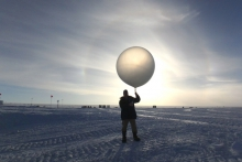 Steve Kirsche prepares to launch a radiosonde (weather balloon) at Summit Station, Greenland. Photo by Heather McIntyre, Courtesy of Steve Kirsche (PolarTREC 2017), Courtesy of ARCUS.