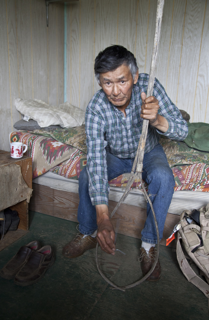 Figure 5. Gwich'in elder Paul Herbert demonstrates a traditional method for dip-netting muskrats from under the ice at his cabin in Chalkyitsik, Alaska. Paul is a long-term contributor to this research. Photo courtesy of Chris Cannon.