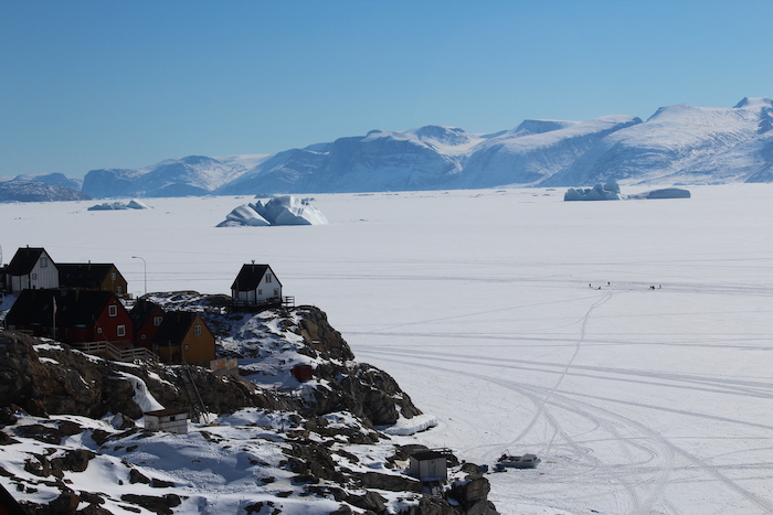 Figure 2. Houses overlooking the sea ice and icebergs. Note the trails formed on the sea ice by dog sleds and snowmobiles and a small group of fishermen on the ice in the right of the image. Photo courtesy of Sarah Cooley