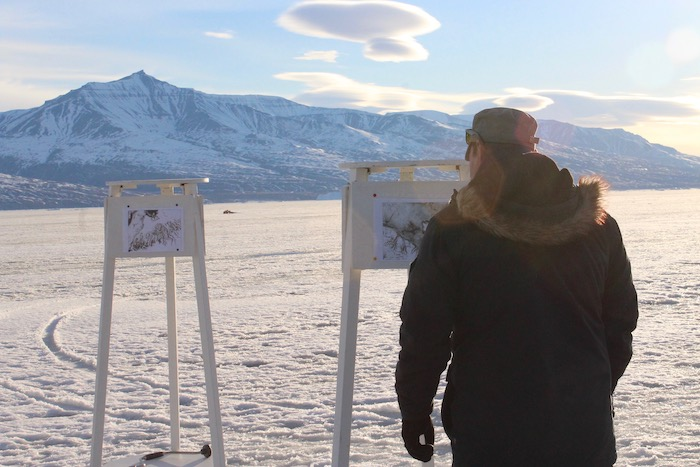 Figure 3. A local collaborator takes a look at some satellite images showing breakup of shorefast ice in Uummannaq Bay from last year in 2018. Photo courtesy of Sarah Cooley.
