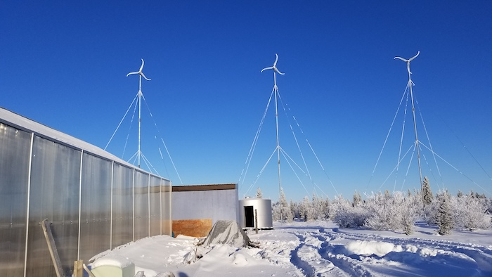 Figure 2: Wind turbines near a greenhouse in Igiugig, Alaska in January 2020.  These turbines are mobile enough to fit on airplanes that service rural Alaska and provide energy for the community. Photo courtesy of Jennifer Schmidt.