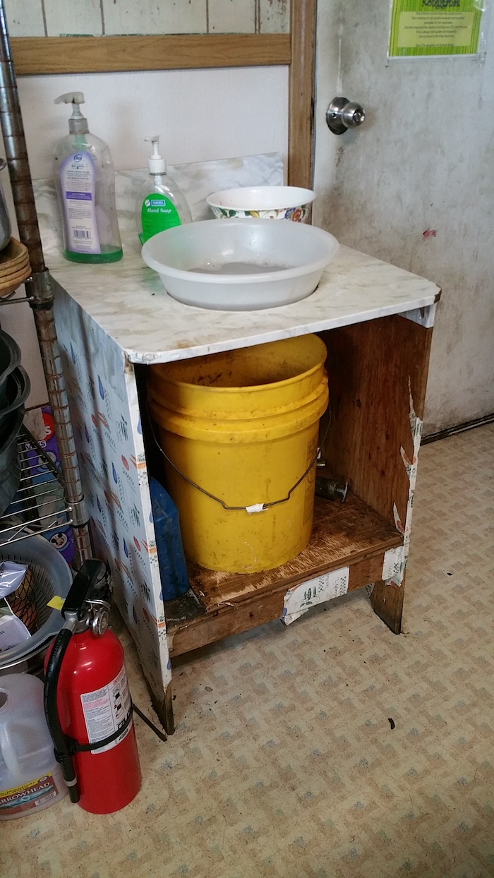 Figure 3: Hand washing basin in Kongiganak, Alaska where there is no indoor plumbing.  Currently the community is working to find an engineering solution to provide sustainable indoor plumbing.  Photo courtesy of Jennifer Schmidt.