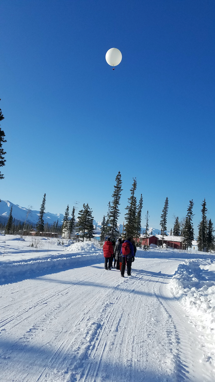 "Figure 5. One activity we do with kids in villages is to take aerial snow photographs using a helium balloon, here being ""walked"" by the kids in Tanacross, Alaska. Photo courtesy of M. Sturm."