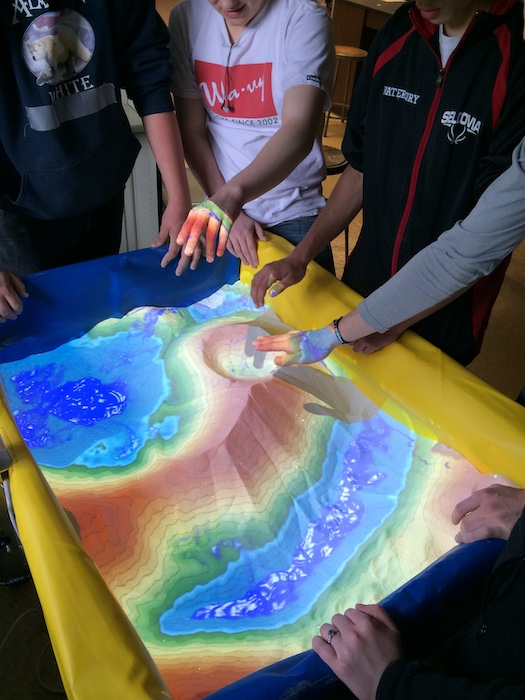 Students in Seldovia experiment with an Alaska ACE Augmented-Reality Sandbox as part of a Kachemak Bay National Estuarine Research Reserve (KBNERR) Discovery Lab in May 2015. KBNERR was a key outreach partner of ACE's Southcentral Test Case, while the sandboxes were a focus of the ACE education component. Photo courtesy of Courtney Breest/Alaska NSF EPSCoR.